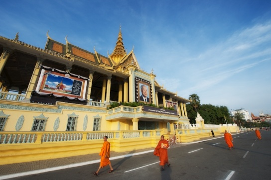 Monks walk past the Royal Palace with images of the deceased King Sihanouk